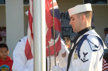 Master at Arms 3rd Class Randy Christensen (right) and Master at Arms 2nd Class Clinton Reese conduct morning colors at St. Theresa's Catholic School during a Veterans Day celebration. Ten sailors assigned to the Pacific Missile Range Facility participated.
