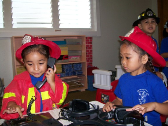 Cheyla Defries and her firefighter buddy, Erianna Garces, pretend to call everyone to invite them to the K.I.D.S. Carnival. Courtesy photo