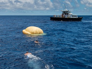 Two members of the Navy's Explosive Ordinance Disposal swim towards the test vehicle. In the background is the recovery vessel Mana'o II.