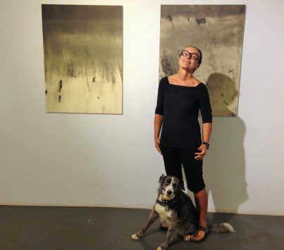 Artist Bruna Stude, owner of Galerie 103 in The Shops at Kukui'ula, poses with Brolie by two pieces from her Empty Ocean Series, Water #4 and #9. For more than 20 years, she photographed sharks, fish and corals. Today, she finds void and damage instead, 'footprints where we humans shouldn't have left any.' That's why she photographs empty oceans. Yet, her art is not a documentation, it's rather an 'artistic choice to illuminate.'