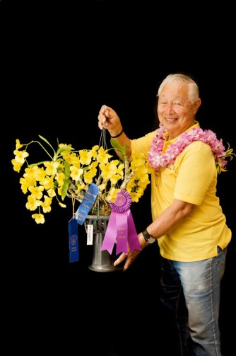Allen Yamada holds his Dendrobium Golden Aya, awarded Best of Show in the 2013 Annual Spring Fantasy Orchid Show.