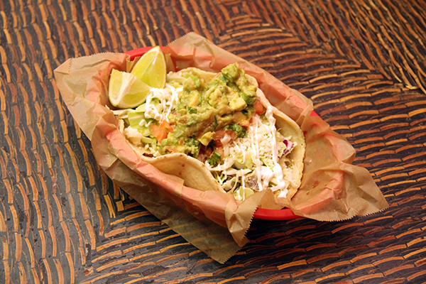 Fish tacos with a side of guacamole on top