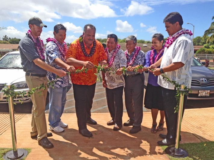 Mayor Bernard Carvalho, Jr. unties the maile lei marking the completion of the Kekaha Gardens' Kaleimanu Park. From L to R: Brian Van Gorp; Brian Low, Mayor Carvalho; Councilmember Ross Kagawa; Harold Tomimitsu; Kaulana Finn; and Lenny Rapozo.