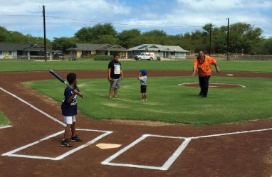"""Mayor Bernard Carvalho, Jr. throws the """"first pitch"""" at the newly completed Kekaha Gardens' Kaleimanu Park. On the field with the Mayor are Makaio and Marques Hickson and Loea Pantohan."""