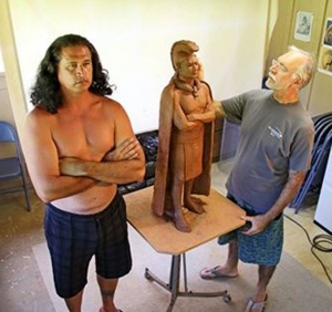 Hawaiian language translator Keao NeSmith is seen here posing for King Kaumuali'i's statue while artist Saim Caglayan works  on it in September 2014.