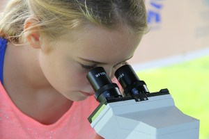 Leela Henderson looks at a microscope.