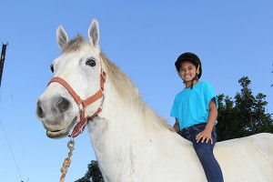 Leina'ala Maka-Adrick is seen here riding D'Artagnan, an 18-hand Percheron and the tallest horse on Kaua'i.