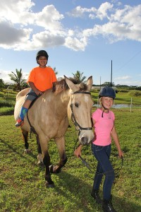 Jose Valenzuela-Perez rides his favorite horse, Duchess, while Ruby Arnold helps by walking them.