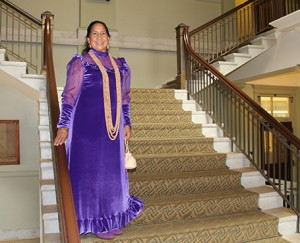 Hau'oli Wichman dons the holokū she wore to a white tie event in England in 2008.