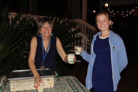 Helaine Perez, GM of The Shops at Kukui'ula, handling popcorn to Halli Holmgren.