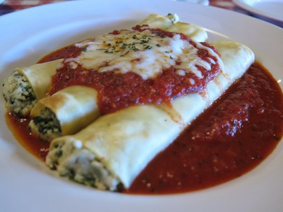 "Manicotti. I can never have enough of these. It's a crepe stuffed to an overflowing blend of cheeses — heavy on the ricotta — spinach and other greens. The filling is fluffy and not heavy at all, and the sweet tomato sauce, ""liquid gold,"" keeps it all warm. This is the height of comfort food, the Italian version of the baked enchilada."