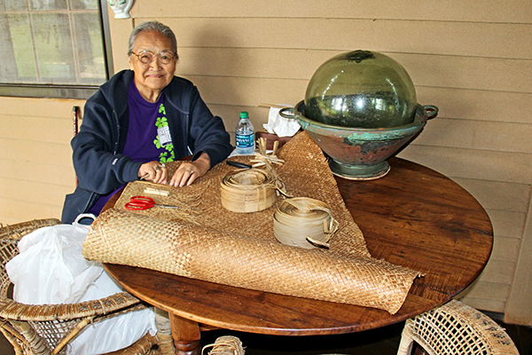 Tomi Kelekoma restores a lauhala mat on the porch of the Grove Farm Museum in Lihu'e.