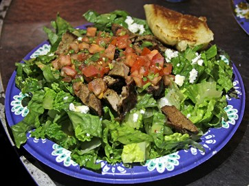 Paniolo's Tri-tip Steak Salad. A hearty salad served with housemate dressing and a dollop of salsa.