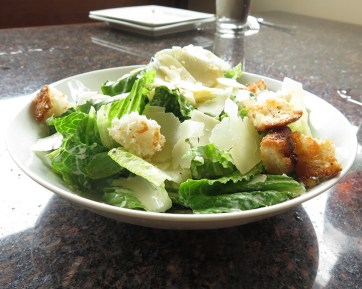 A Caesar Salad pairs well with pizza. This one features cheesy housemade croutons and shaved parmesan with a tangy and garlicky dressing.
