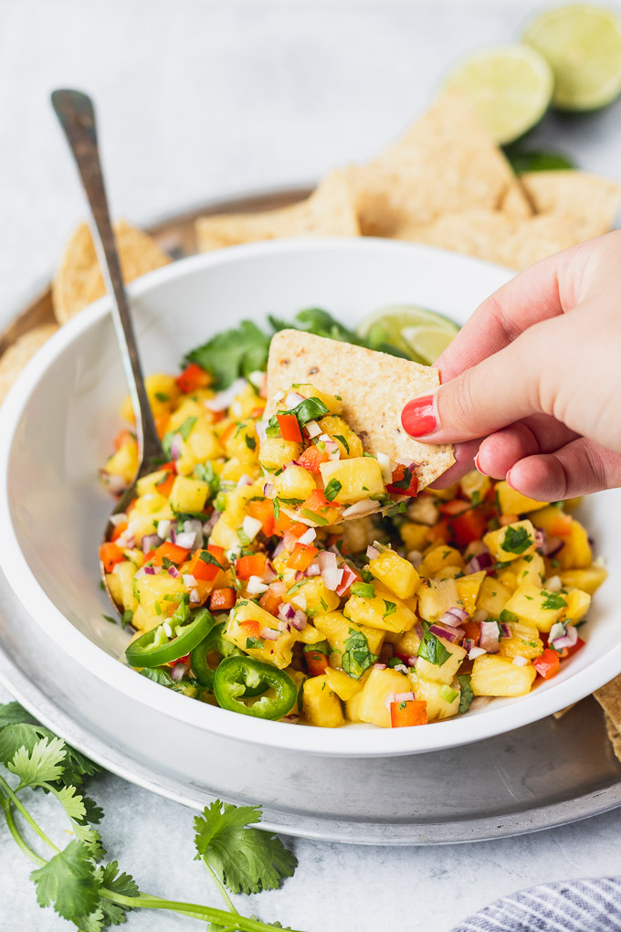 chip dipping into pineapple salsa