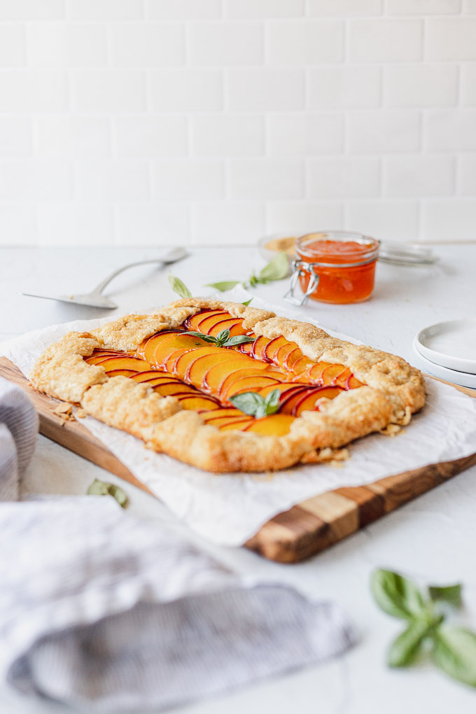 peach galette on cutting board with linen