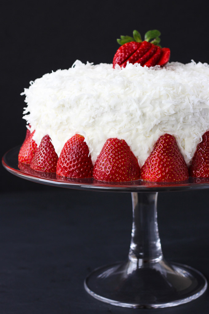 Strawberry Coconut Cake - moist, heavenly cake with a creamy coconut frosting, topped with fresh strawberries and a strawberry sauce! Perfect for any occasion!