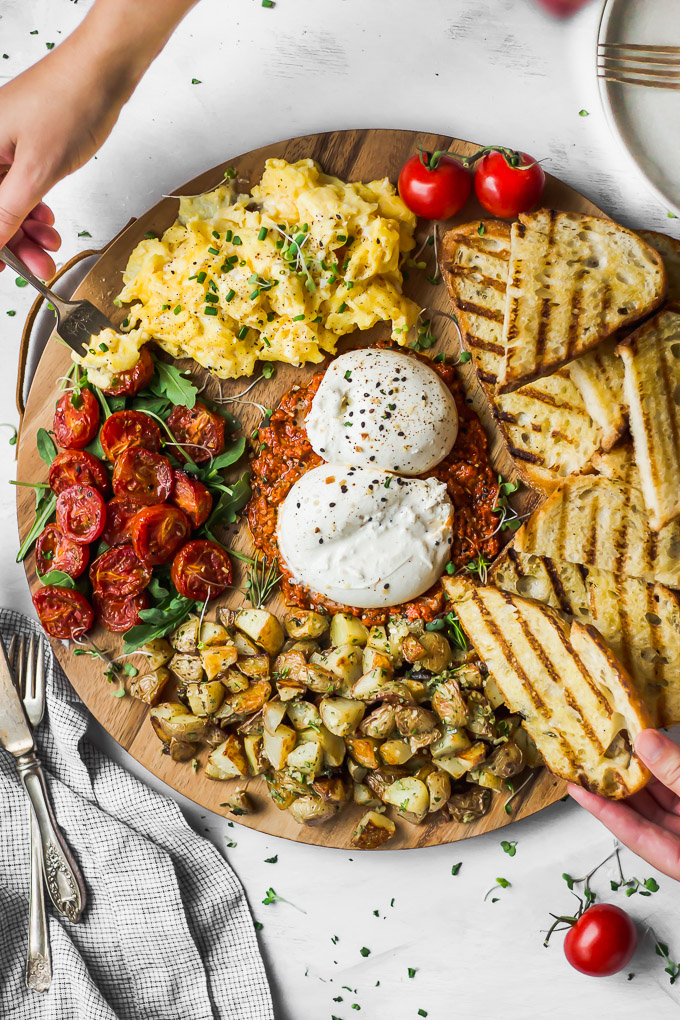 hands reaching on burrata breakfast board with toast, eggs, tomato