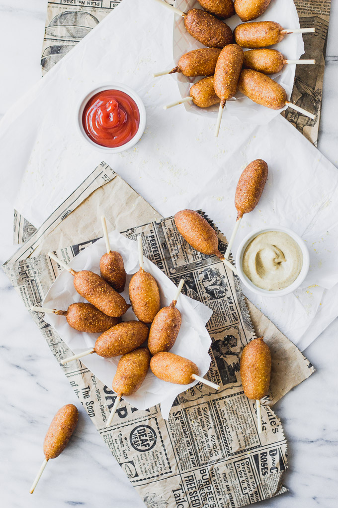Overhead view of Mini Carrot Corn Dogs in serving container with ketchup and mustard on newspaper