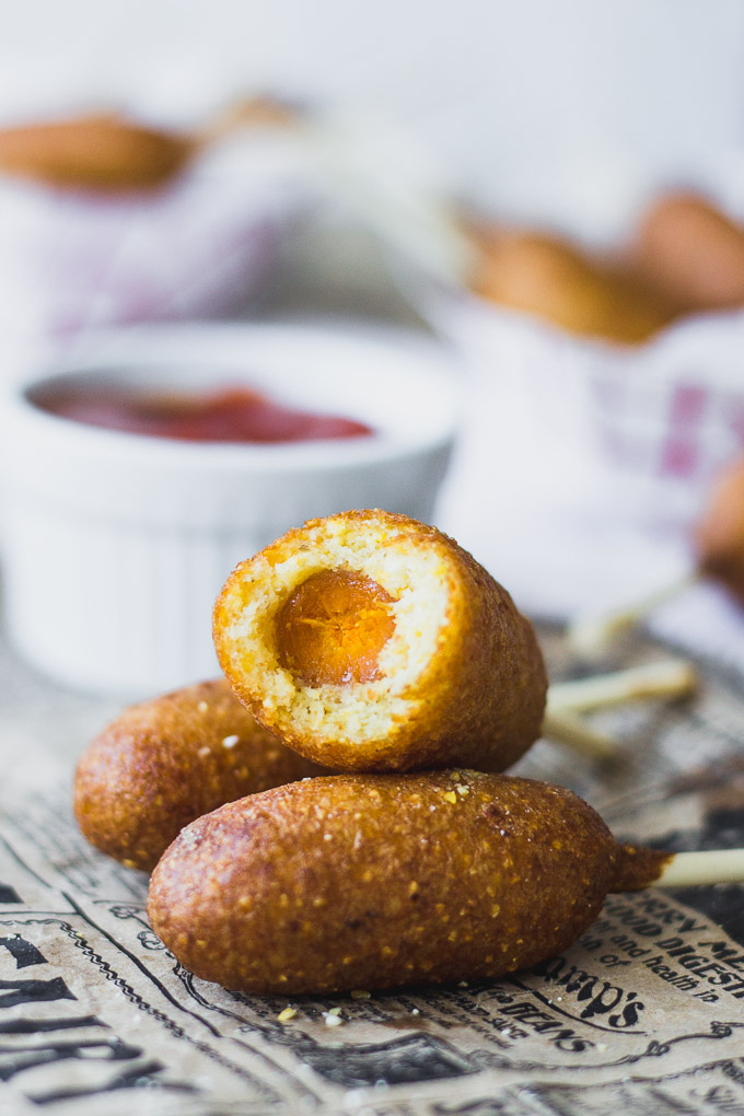 side view of Mini Carrot Corn Dogs piled on with a bite taken