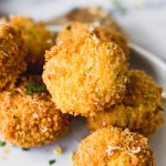 scalloped corn arancini piled on white plate
