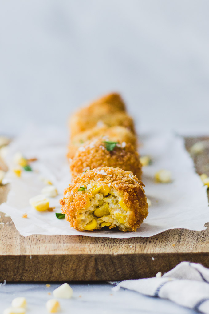scalloped corn arancini with bite out lined on serving platter