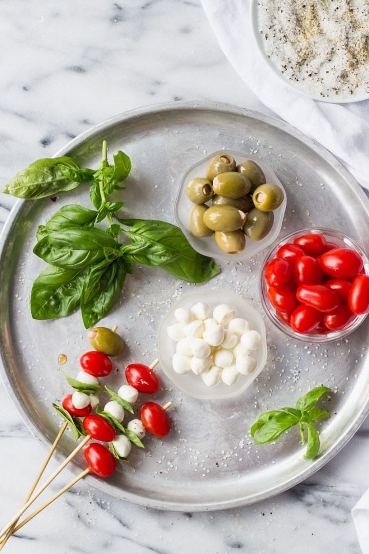 overhead of tray with tomatoes, basil, mozzarella, olives, and skewers