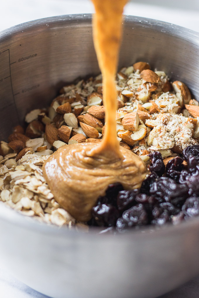 almond butter mixture pouring into ingredient bowl
