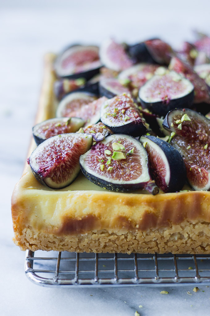 side shot of honey cheesecake bars with figs and pistachios