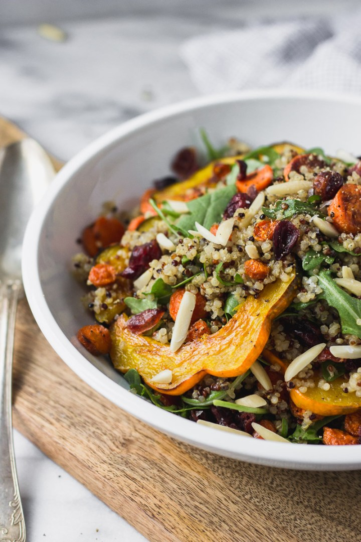fall acorn squash salad with carrots and arugula in white bowl with spoon by fork in the kitchen