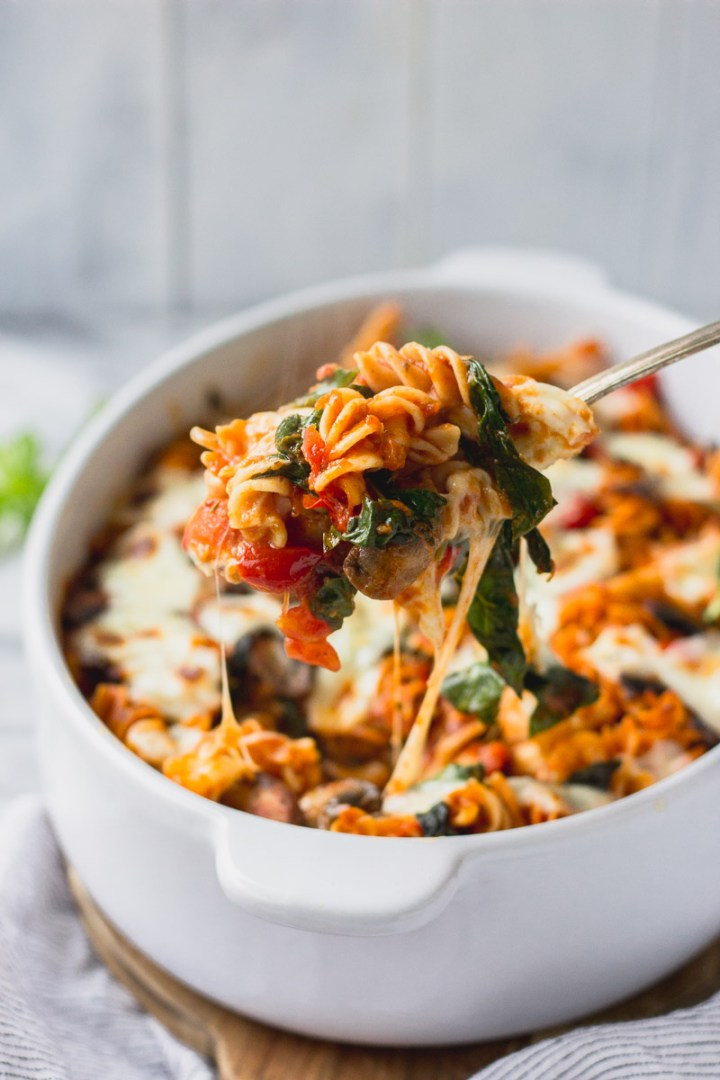 vegetable baked pasta in white casserole dish with scoop being lifted