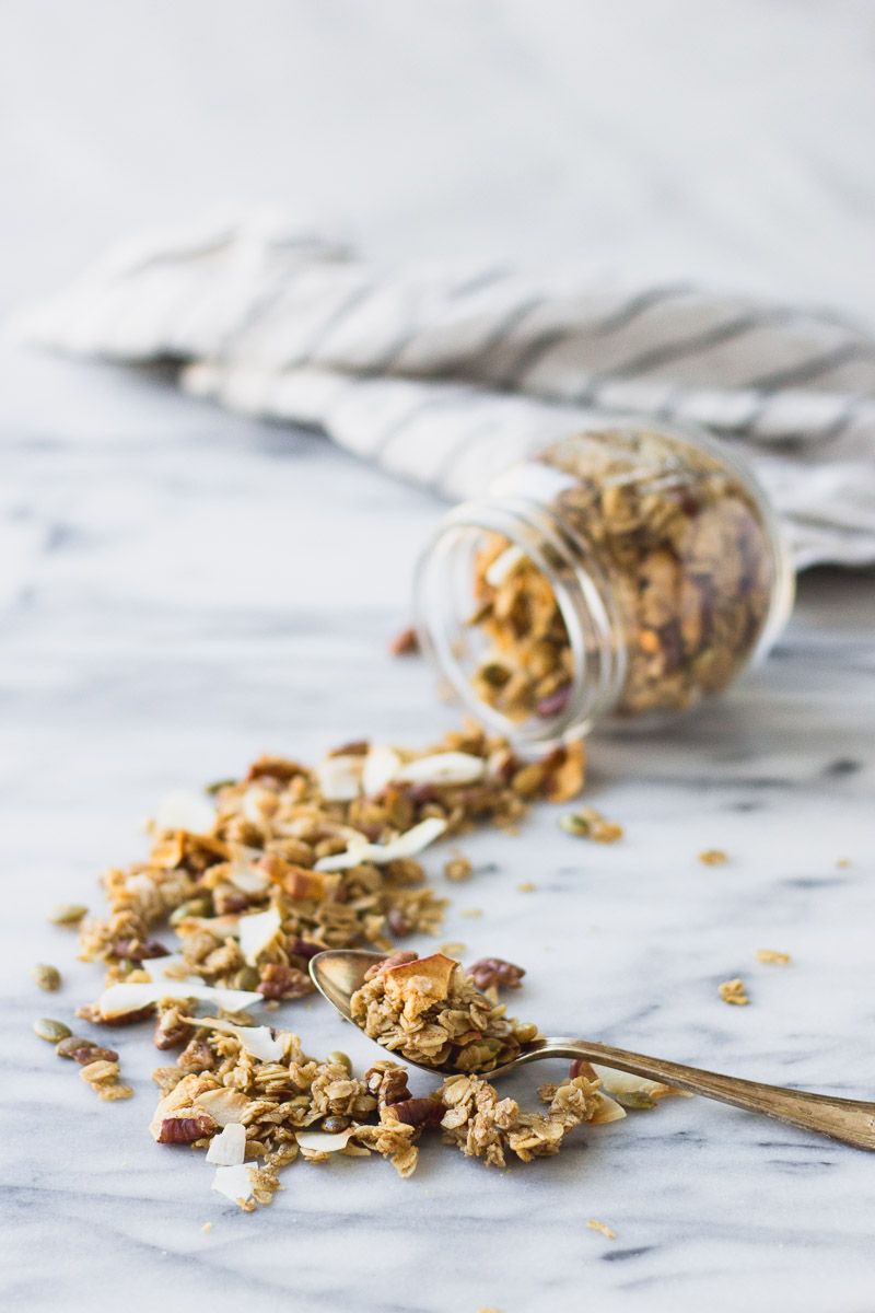 easy autumn spice granola pouring out of jar by fork in the kitchen