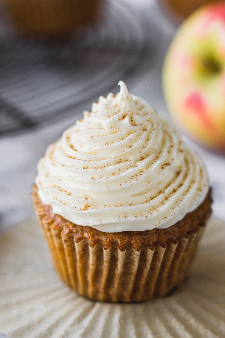 apple cider cupcake with bourbon cream cheese frosting on liner next to apples and cooling rack by fork in the kitchen