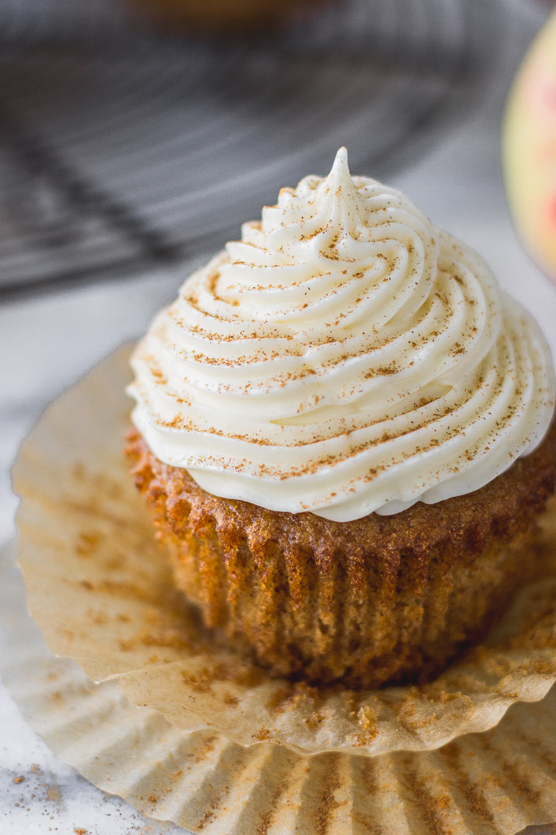 apple cider cupcake with bourbon cream cheese frosting on liner by fork in the kitchen