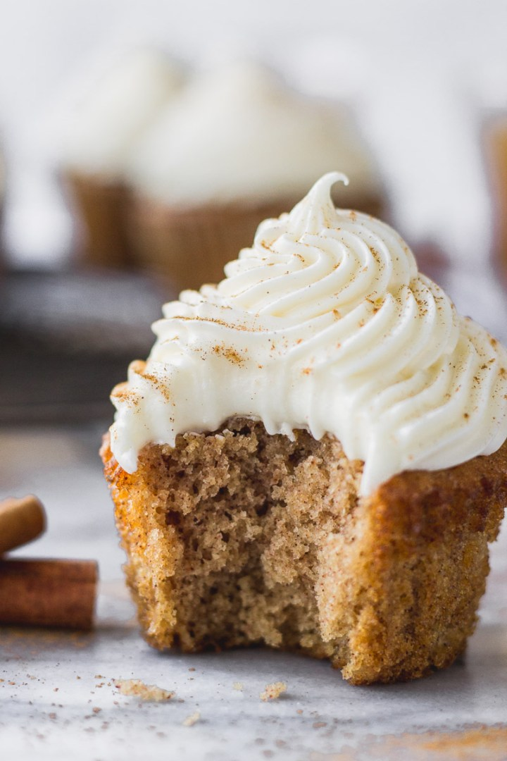 apple cider cupcake with bourbon cream cheese frosting on liner with bite removed and cooling rack by fork in the kitchen