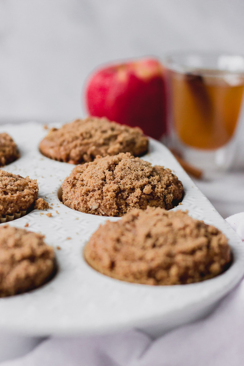 apple cider streusel muffins in muffin pan by fork in the kitchen