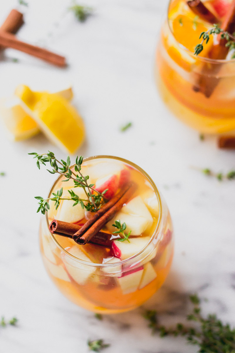 apple cider sangria in glass with cinnamon, thyme, and apples by fork in the kitchen
