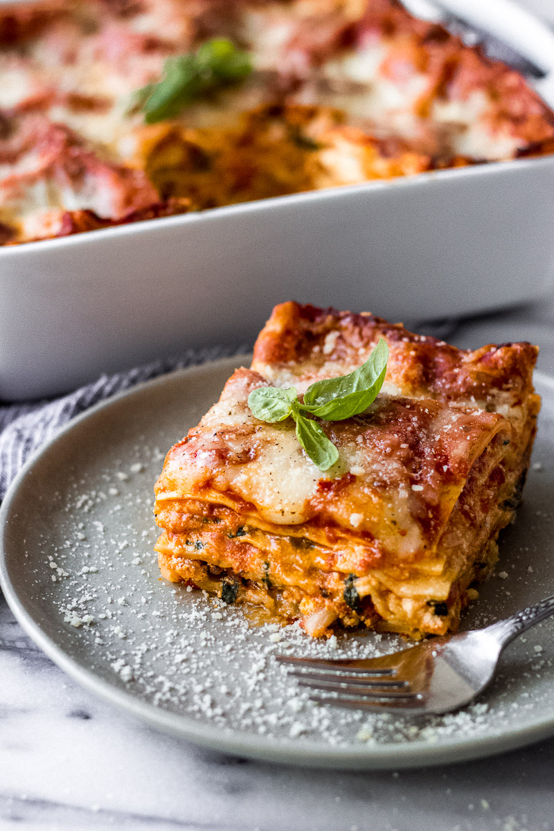 Vegetarian Spinach Ricotta Lasagna slice on gray plate with fork by Fork in the Kitchen