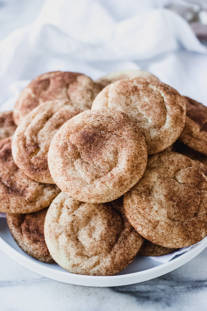 spiced snickerdoodle cookies on serving white plate by fork in the kitchen