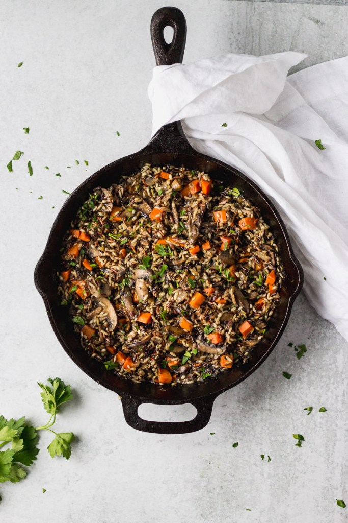 Herbed Wild Rice with Mushrooms in cast iron skillet by fork in the kitchen