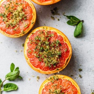 broiled grapefruit with mint and sugar by fork in the kitchen