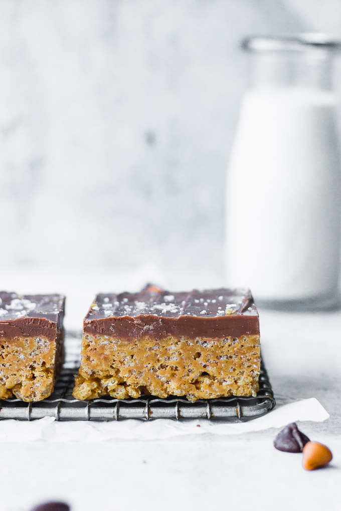 chocolate butterscotch rice krispie bars on cooling rack stacked with milk