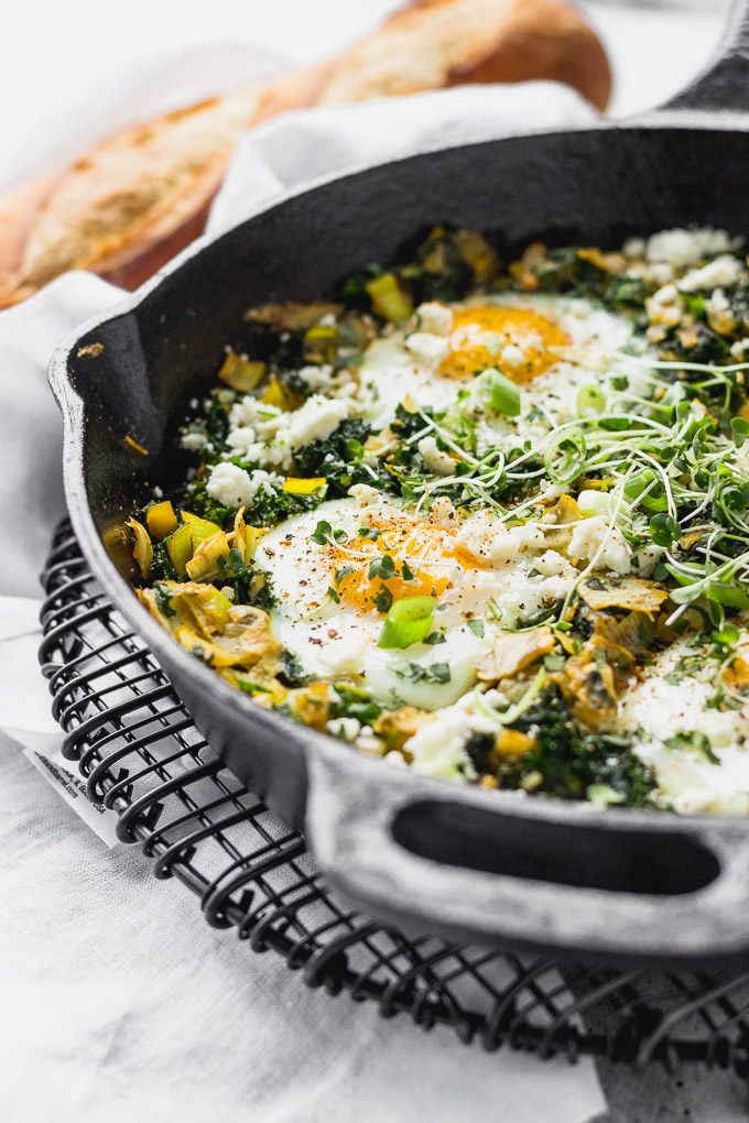 green shakshuka in skillet with spoon