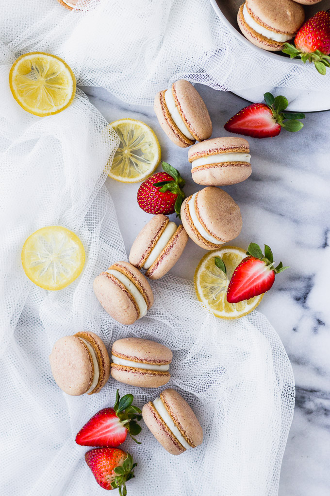 strawberry macarons spread out on marble board