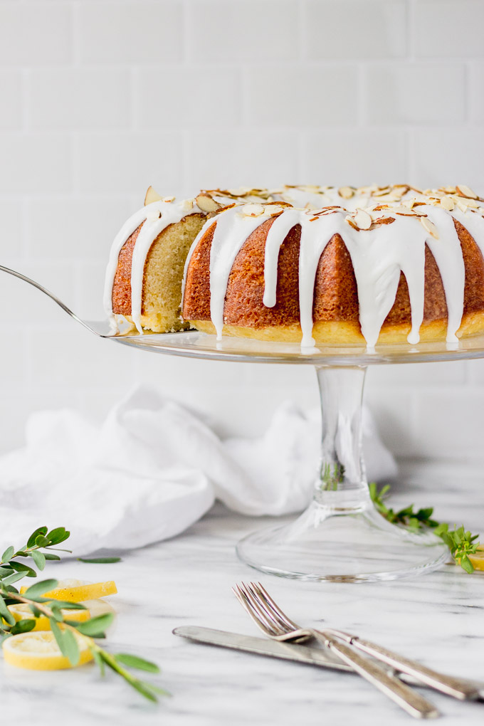 lemon almond cake on clear cake stand with server