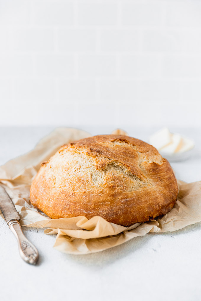french bread loaf on parchment paper with knife