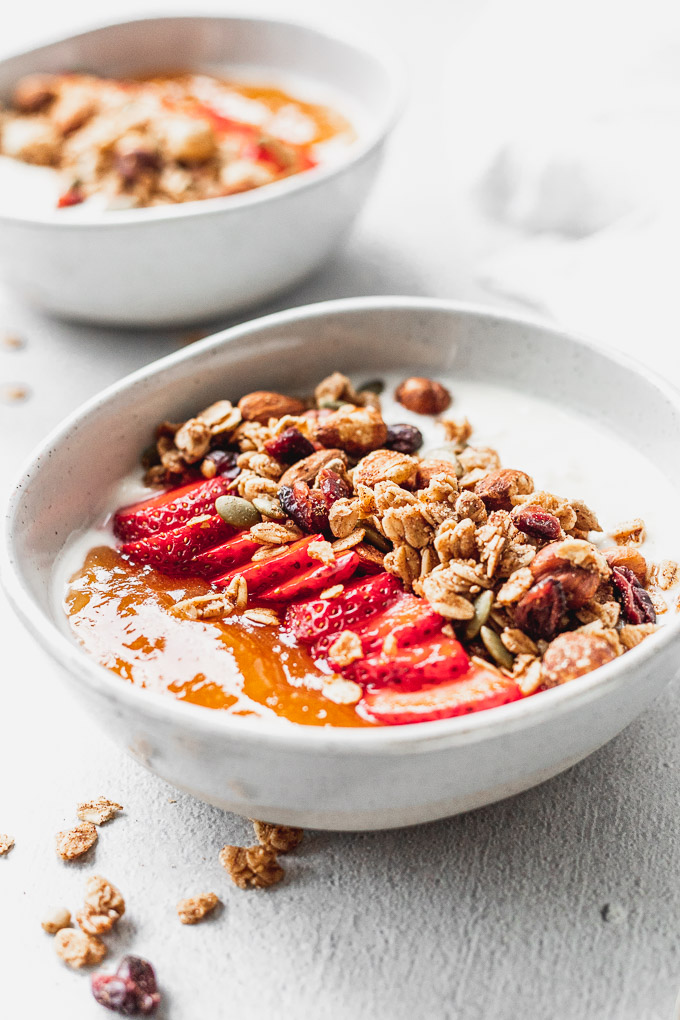 bowl of cinnamon granola with strawberries and apricot jam