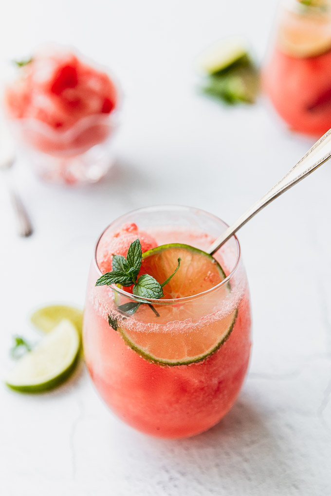 wine glass with watermelon granita, mint, and a lime with a spoon