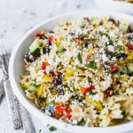mediterranean pasta salad in white bowl with forks