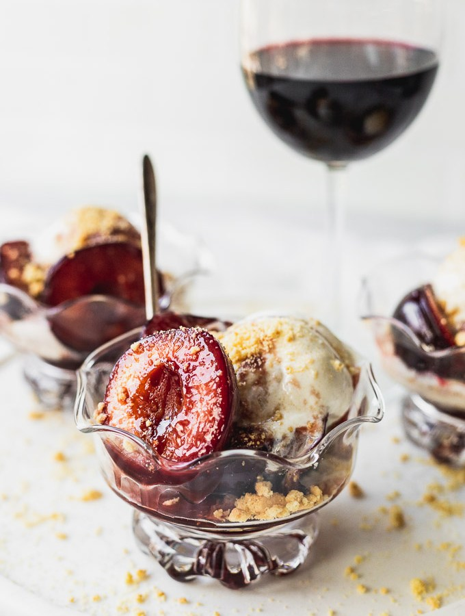 bowl of plums with ice cream and wine sauce with spoon